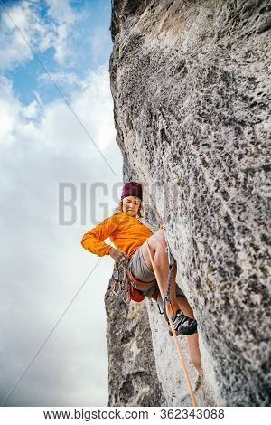 Young Athletic Woman Climbs An Overhanging Rock With Rope In Crimea. Sport Climbing, Lead. Side View