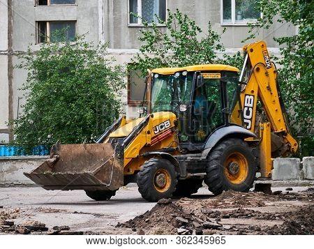 Kharkov, Ukraine - March 2020, Hydraulic Excavator Removing Remains Of Asphalt. Road Reconstruction.