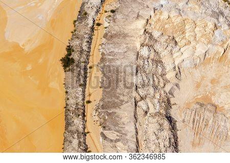 An Arid Wind Swept Patch Of Orange Dirt In A Dry Unused Waterway.
