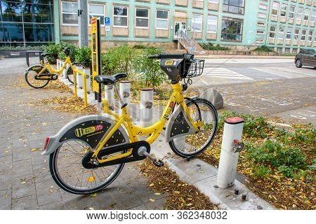 Bratislava (slovakia)- October 06 2019: Yellow Public Bike Locked In Docking Station Near Parking Lo
