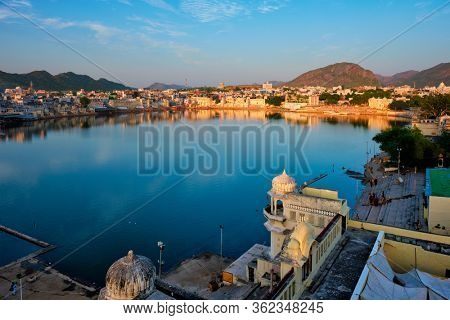 View of famous indian hinduism pilgrimage town sacred holy hindu religious city Pushkar amongst hills with Brahma mandir temple, lake and traditional Pushkar ghats at dusk sunset. Rajasthan, India