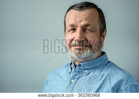 Elderly bearded smiling man in a shirt close-up portrait