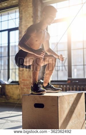 Side view of jumping young sportsman on wooden box in gym against background of large window, lensflare effect