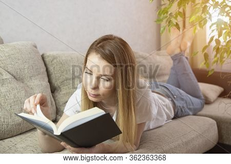 Happy Young Woman Reading Storybook On Couch At Home.