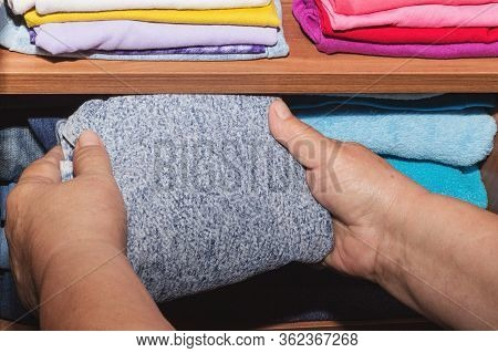 Woman's Hands Put Baby Clothes In The Closet. Storage Of Clothes, Cleaning, Cleaning Concept. Hands