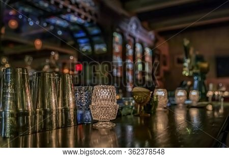 Vintage Wooden Bar Counter With Candles In Glass Holders, Bar Tools And A Blurred View Of A Baroque