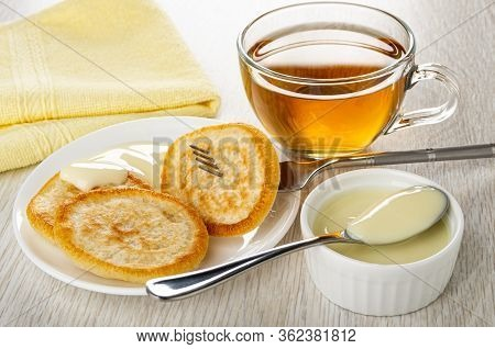 Yellow Napkin, Transparent Cup With Tea On Saucer, Pancake Strung On Fork, Pancake With Condensed Mi