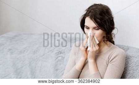 Sick Woman Suspected Of Covid-19 Being At Home In Bed Sneezes. Closeup Sick Girl Sneezes In Handkerc