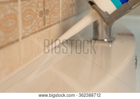 Use Of Silicone Or Sealant For Fixing A Sink In Bathroom Close Up