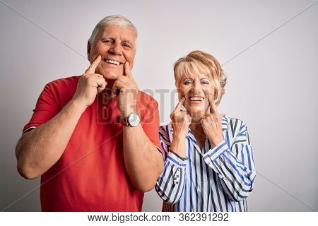 Senior beautiful couple standing together over isolated white background Smiling with open mouth, fingers pointing and forcing cheerful smile