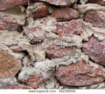 Wall Of Pink Rough Granite Stone And Cement Mortar. Rubble Masonry. Background Texture For Design.