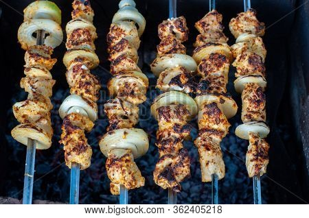 Top View Of Homemade Chicken Shish Kabobs With Fresh Onions. Grilled Chicken Meat Skewers On Dark Ba