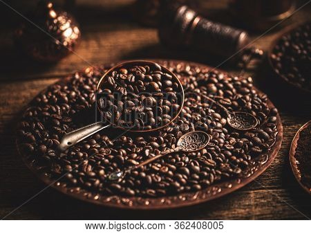 Coffee Beans In Copper Plate With Antique Spoon On Wooden Background, Dark Toned