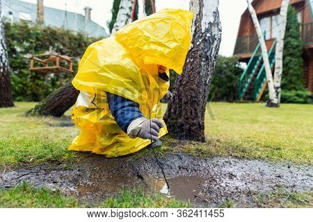 Cute Adorable Caucasian Toddler Boy In Bright Yellow Raincoat And Wellies Playing Alone At Dirt Mudd