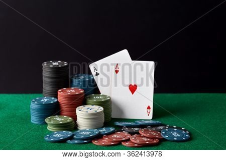 Poker Chips And Cards On A Green Poker Canvas. Gambling, Poker, Casino Concept. Black Background. Cl