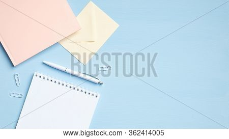 Modern Office Desk Table With Blank Notepad, Pink Paper Notebook, Envelope And Other Supplies On Blu