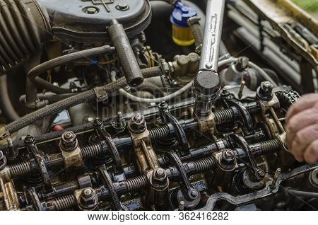 The Procedure For Tightening The Cylinder Head Bolts. Part 4 Of 6. The Man Manually Tightens The Nut