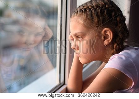 Tired Of Self-isolation, A Bored Quarantine Girl Looks Out The Window