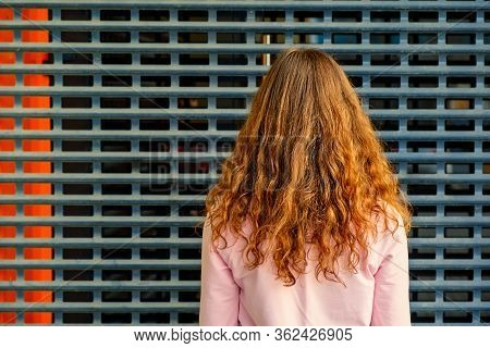 The Back View Of A Girl Standing In Front Of Metal Grid Wall