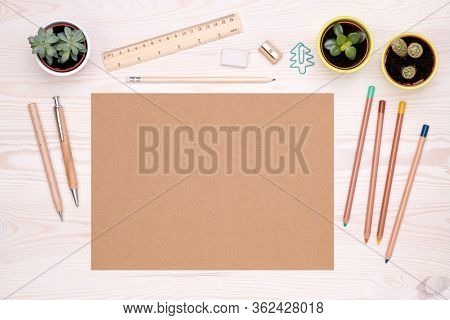 Desk top with eco friendly office supplies such as wooden pen, pencils and piece of brown paper with copy space