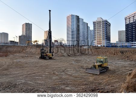 Tracked Pile-driver And Bulldozer At Construction Site On Sunset. Piles Driven Into The Ground By Vi