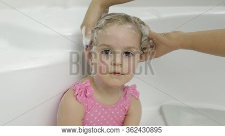 Attractive Four Years Old Girl Takes A Bath With Bath Foam In Pink Swimwear. Mother Washes Her Daugh