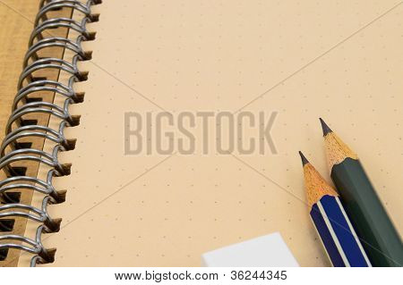 Two Wooden Pencil And Eraser On Recycle Notebook Background.