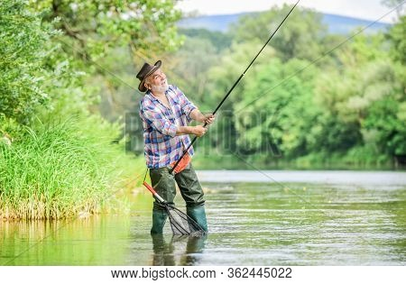 Fishing Is Fun. Mature Man Fly Fishing. Man Catching Fish. Summer Weekend. Big Game Fishing. Retired