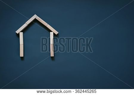 House Of Wooden Blocks On A Blue Background, Roof And Walls The Concept Of Real Estate, House Buildi