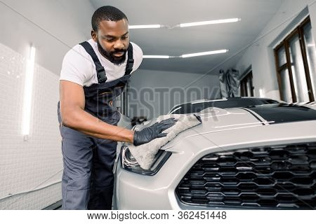 Young Handsome African Car Wash Worker Man, Wearing Protective Clothes And Gloves, Wiping Headlight