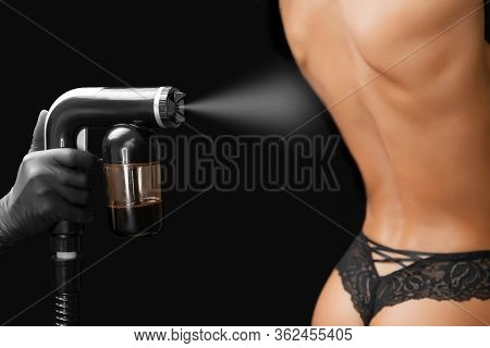 Woman Body Paint Instant Tan Spray Skintone With Airbrush In Professional Beauty Salon On Black Back