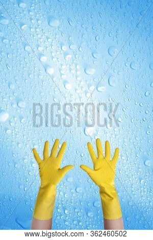 close up hands wearing yellow cleaning gloves over water drops covered background