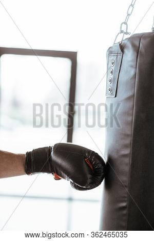 Cropped View Of Sportive Man In Boxing Glove Training With Punching Bag