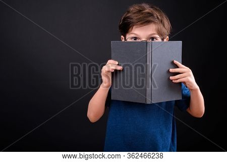 Portrait Of Shy Young Boy Covering Face With Book