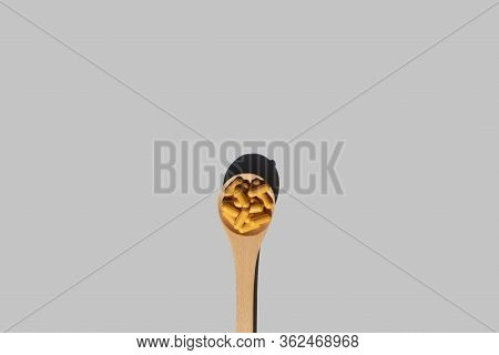 Super Food Concept Wooden Spoon With Turmeric Curcumin Capsules On Grey Background