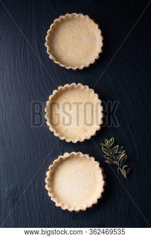 Food Concept Homemade Emty Pie Crust For Organic Lemon, Lime Tarts Or Mini Pie On Black Slate Stone