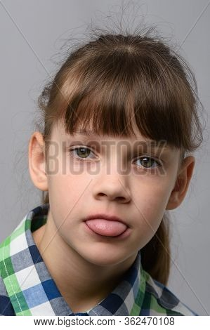 Portrait Of A Ten-year-old Girl Sticking Out Her Tongue From Resentment, European Appearance, Close-