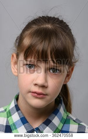 Portrait Of A Perplexed Ten-year-old Girl Of European Appearance, Close-up