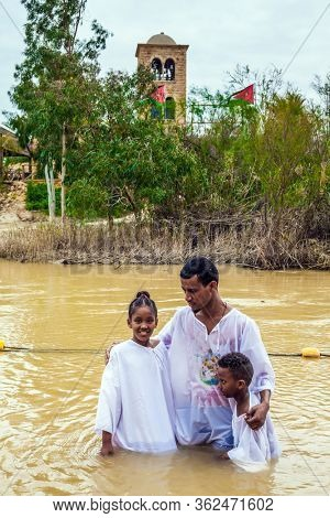 QASR El-YAHUD, ISRAEL - MARCH 2, 2020: Qasr el-Yahud - the place of baptism of Jesus Christ on Jordan River. Baptism of children. Men in white shirt stand in the water and hold the children.