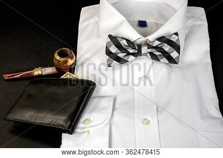 Black And White Checkered Bow Tie On Folded White Dress Shirt With Wallet And Old Smoking Pipe On Bl