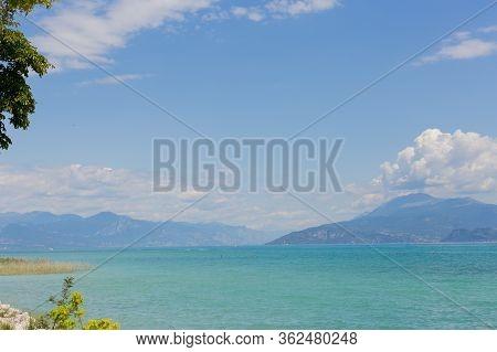 View Of Lake Garda In Italy. Daytime. Calmness. Nobody. Nature. Panoramic View. Blue Clear Water. La