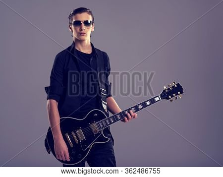 Fifteen years old guitarist with a  black electric guitar. Teenage musician holds guitar, posing at studio. The young caucasian guy with a guitar. Stylish musician. Heavy metal player.