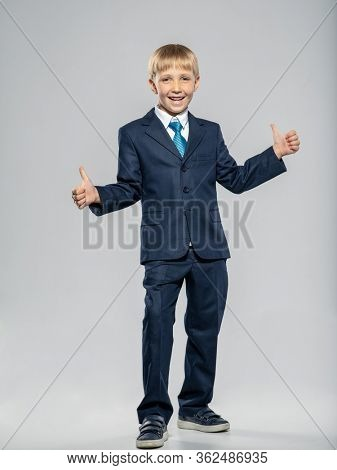 Happy boy in a blue business suit with big thumbs up, posing at studio. Cheerful boy dressed in a formal suit with blue tie showing thumbs up. Photo of  a joyful businessman boy. Full portrait.