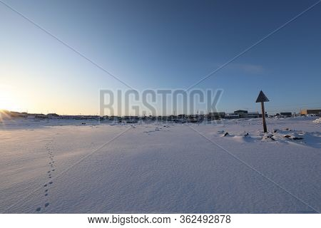 Isolated Arctic Landscape With Inuit Community In The Background And Single Set Of Footsteps In The