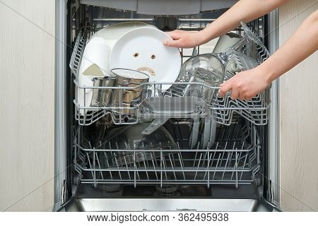 Poorly Washed Dishes In The Dishwasher. Integrated Dishwasher With White Plates Front Vew And Sad Em