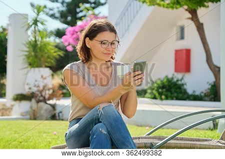 Beautiful Middle-aged Woman Resting Sitting On Sunbed On Green Lawn, Reading Smartphone Using Intern