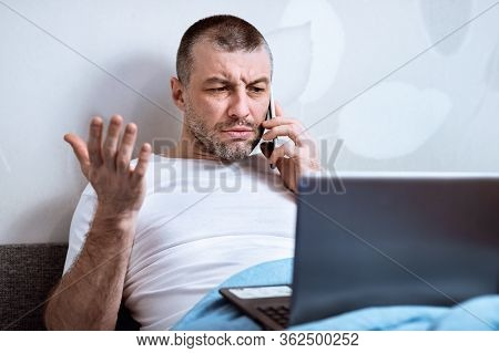 Discontented Man Calling Customer Support Hotline Having Problems With Laptop Sitting In Bed At Home