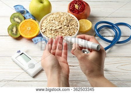 Female Checking Blood Sugar Level On Background With Diabetic Accessories
