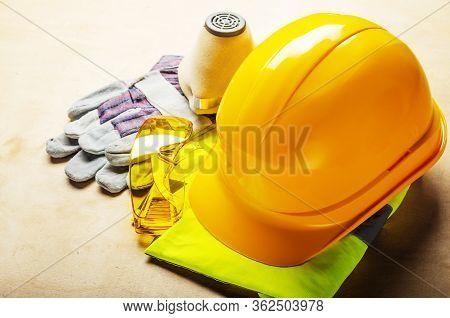 Yellow Plastic Hard Hat, Glasses, Respirator And Protective Gloves Laying On Plywood. Safe Labor Con