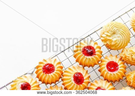 Freshly Baked Sable Cookies With Cranberries Jam And Almonds On Silver Metal Rack And White Backgrou